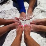 Family feet on the beach