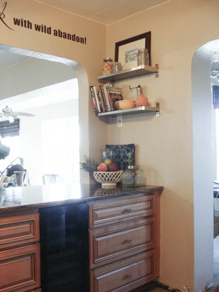 kitchen cabinets with pass through to living room and shelves on the wall to organize a small kitchen
