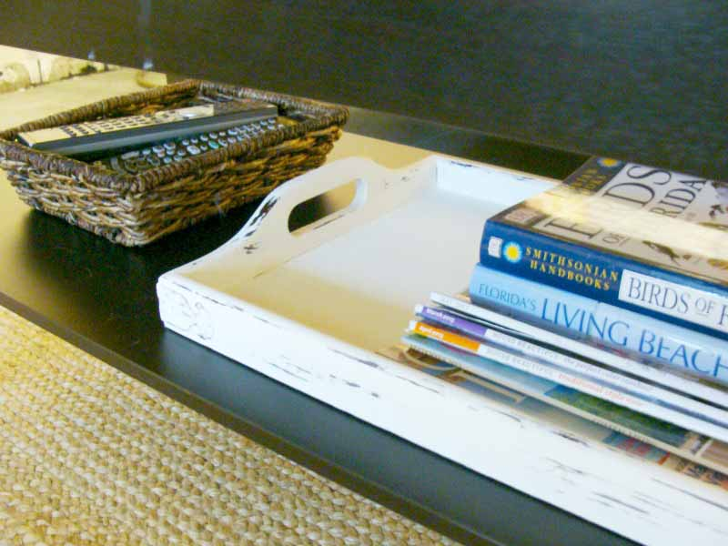 basket of remotes and tray of magazines and books on shelf under coffee table