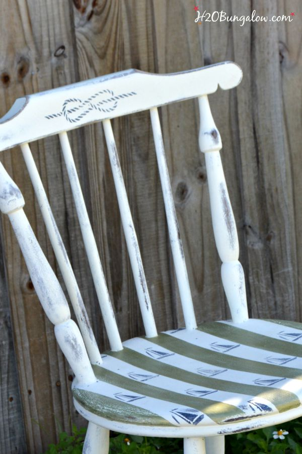 DIY nautical accent chair makeover. Furniture painting tutorial for stripes and sailboat stenciling with resource list. Make your own coastal accent chair. Find more home decor tutorials at H2OBungalow.com