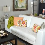 White leather sofa with colorful throw pillows and coffee table