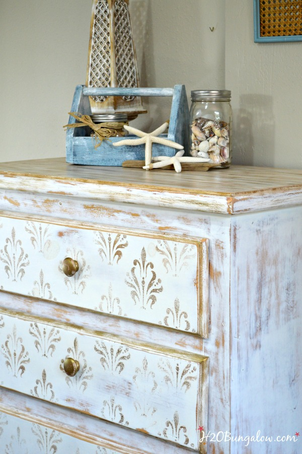 White and gold distressed damask dresser made use of an old family chest and turned it into something I loved and that fit into my house Good tutorial insluded for distressed look H2OBungalow.com #paintedfurniture
