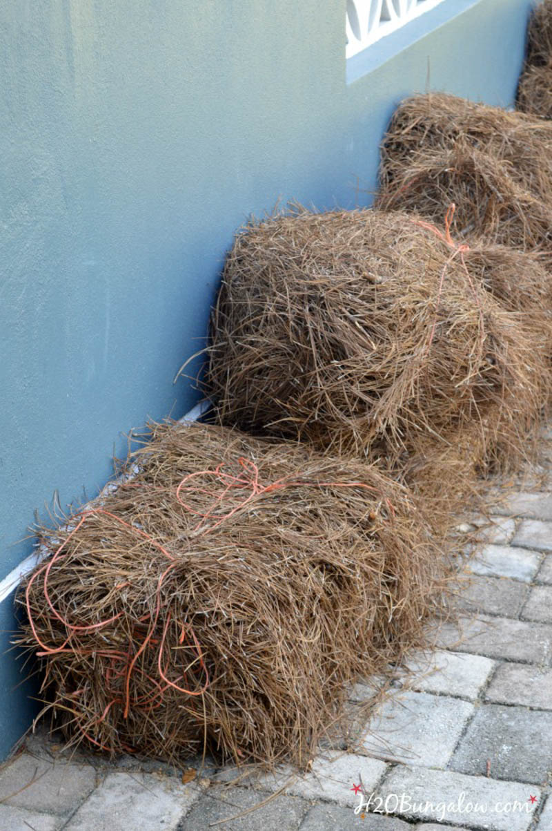 bales of landscaping straw sitting next to the house