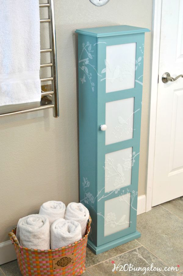 Updated bath storage cabinet with DIY frosted glass inserts and cascading stenciled birds and twigs. It looks fresh and clean look in our new master bath www.H2OBungalw.com #ThemedFurnitureMakeoverDay #painted