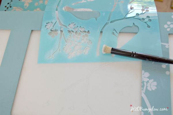layered bird stencils on my bathroom storage cabinet makeover with frosted glass inserts H2OBungalow