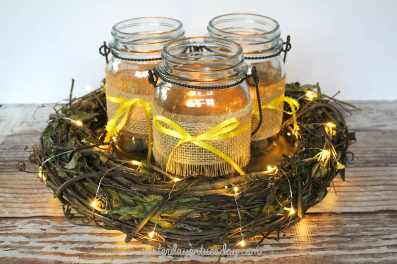 3 mason jars with burlap sleeves sitting in the middle of a wreath wrapped in mini string lights