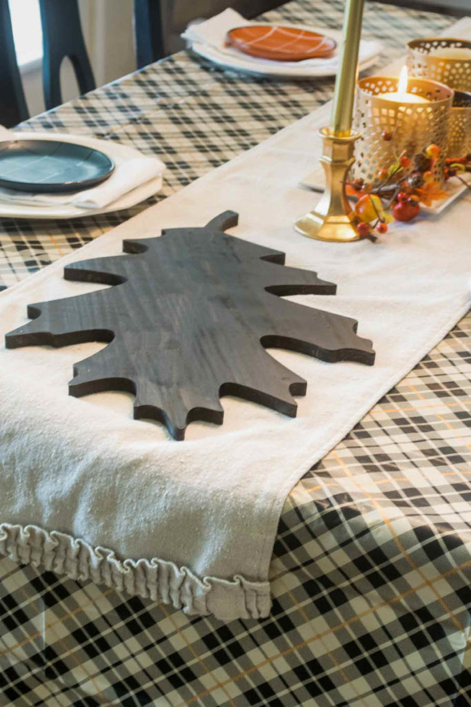 Large wooden leaf shaped tray on a table runner sitting on a plaid tablecloth