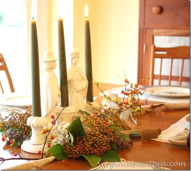 3 candlestick holders and fall floral with pilgrims as the centerpiece
