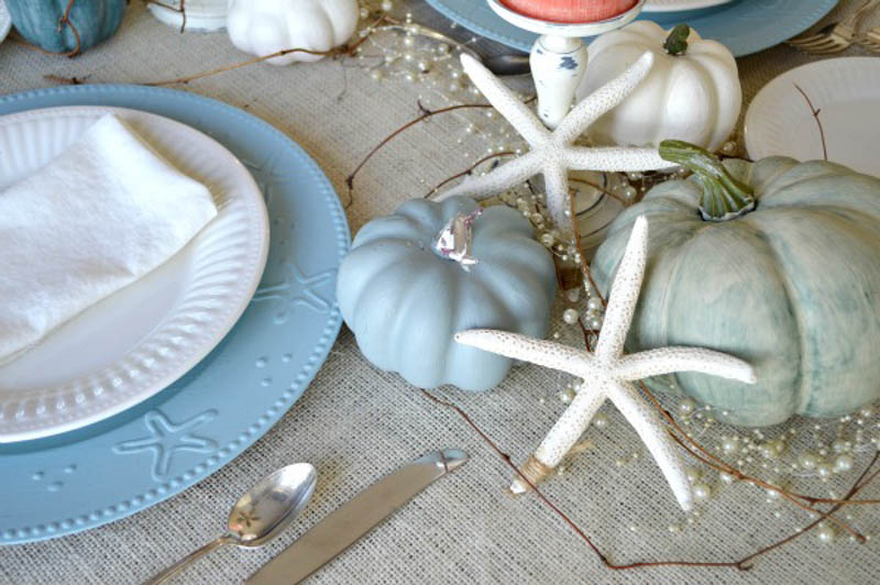 blue and white place setting with painted pumpkins and white starfish