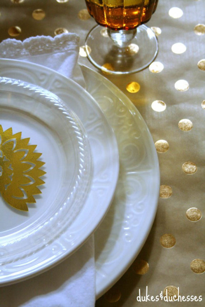 white place setting with metallic turkey place card and metallic polka got table cloth