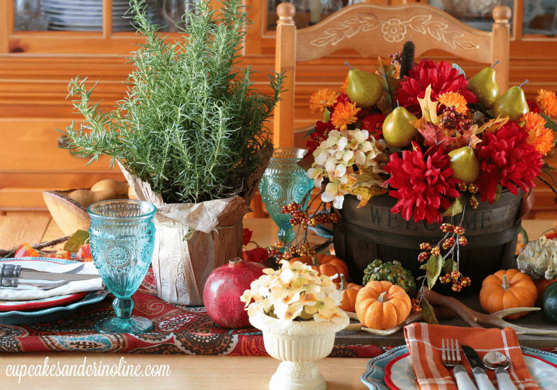Colorful tablescape with red and orange flowers, pumpkins and  mini evergreen in a burlap sack