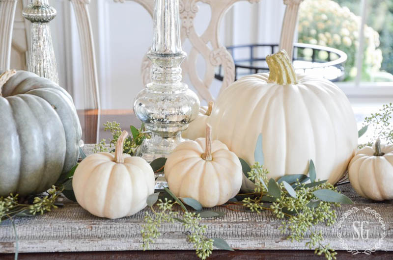 White pumpkins sitting on a table runner with greenery and clear glass candlesticks
