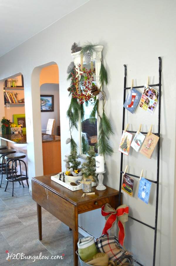 My festive holiday entry makes good use of an entry table in a tight space to stage a warm welcome with a multi-purpose vignette, Christmas cards hang nicely on the metal ladder and a bucket of lap blankets are perfect for a chilly night add to a pretty entry with simple decor. www.H2OBungalow.com #Smallspace