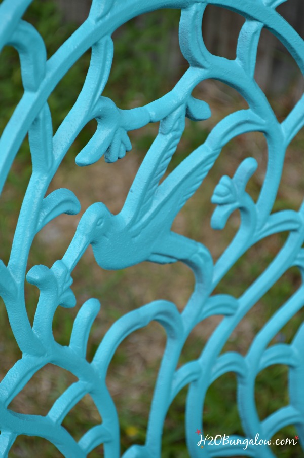 Close up of back of metal chair spray painted turquoise