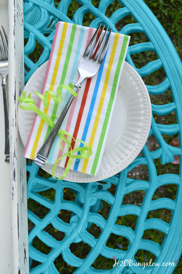 table setting with colorful striped napkin on metal painted furniture