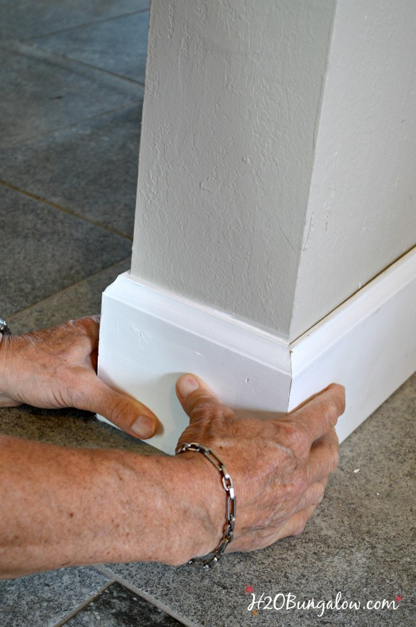 DIY baseboard tutorial shown being installed with two hands holding it.