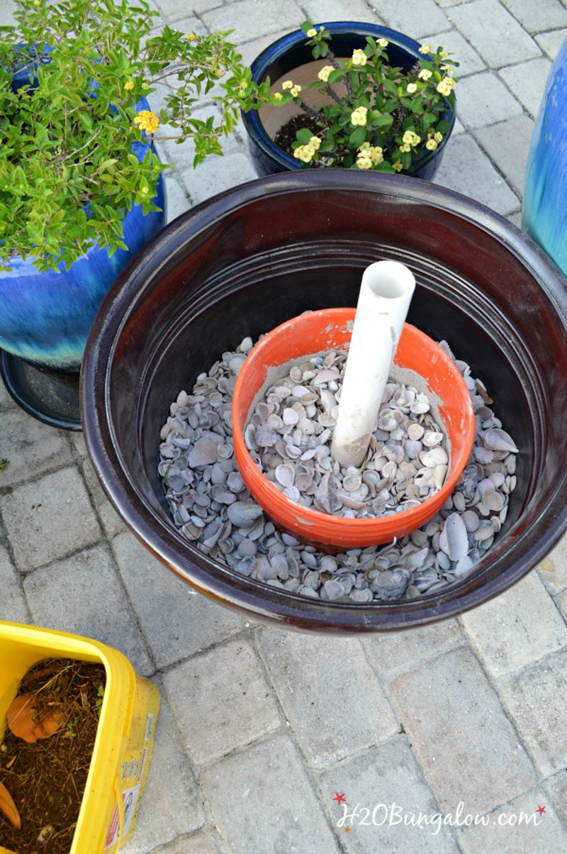 planter with five gallon inside and sea shells used as filler
