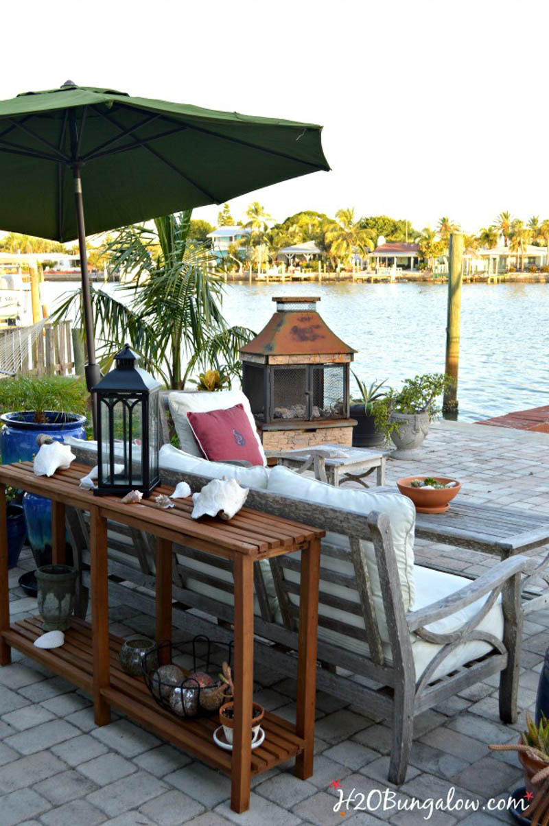 patio with furniture and DIY umbrella plant stand overlooking the water