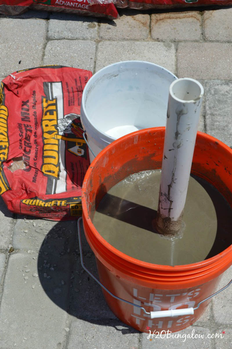 red five gallon bucket with concrete and PVC pipe in it