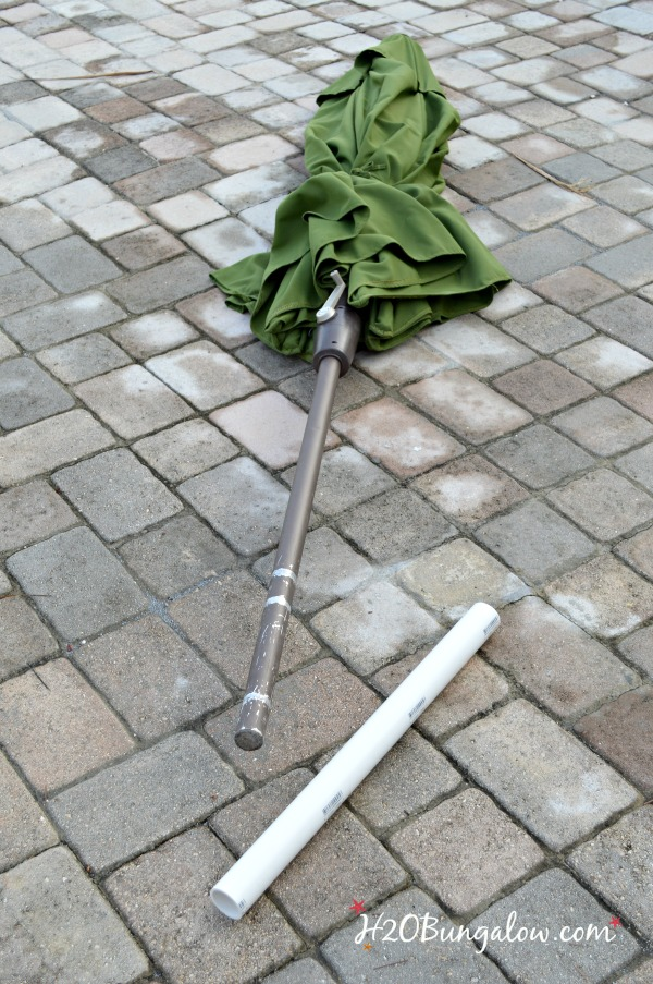 green umbrella shown laying flat on patio