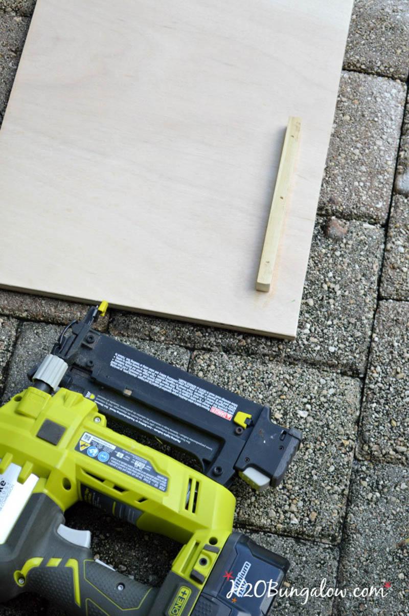 board laying on brick with nail gun