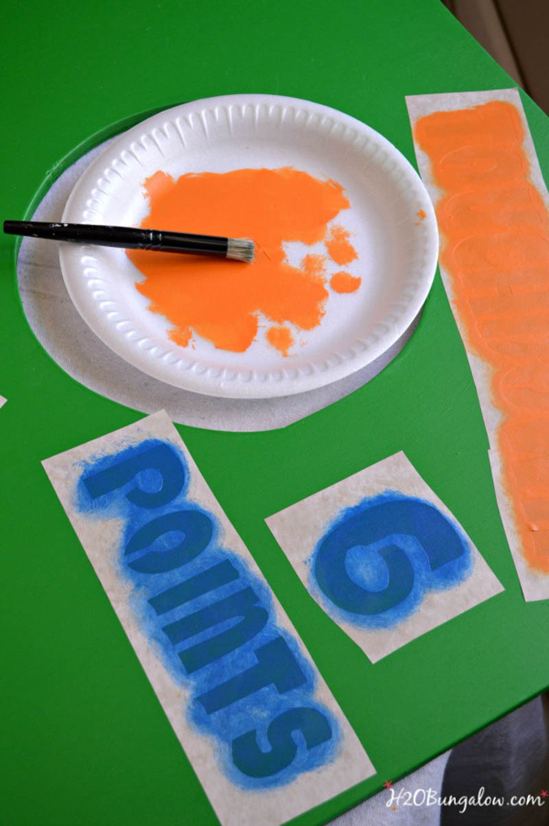 orange stencil paint on paper plate blue painted stencil on green board
