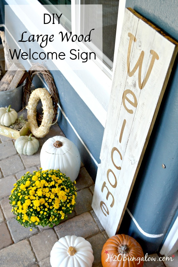 Large wood welcome sign on the porch with pumpkins and yellow mums.