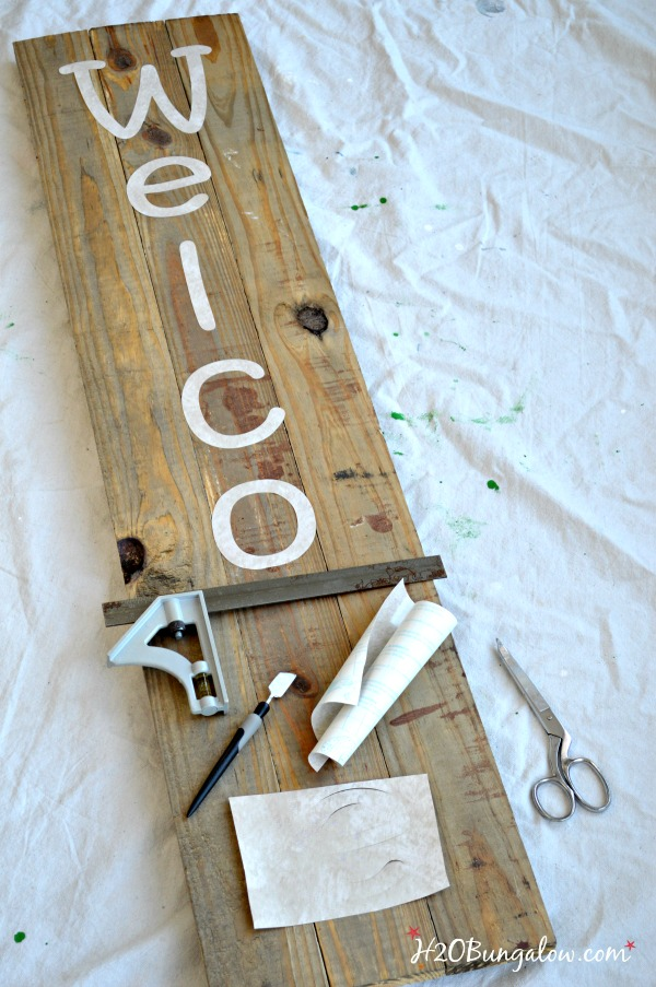 Stencil letters spelling Welcome laying on wood with tools.