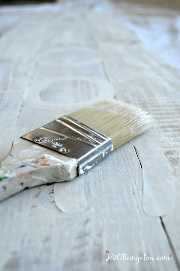 Paint brush laying on dry brushed wood.