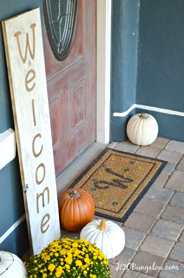 Large wood welcome sign on the front porch with pumpkins and yellow mums