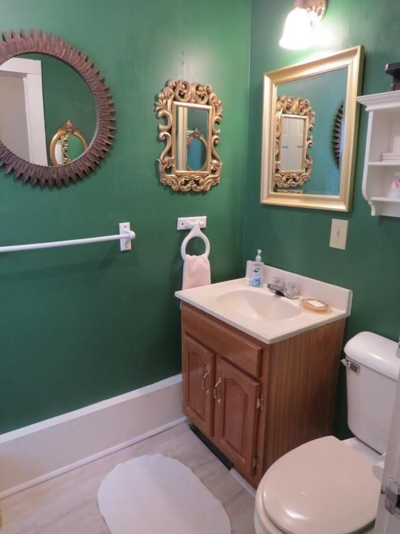 bathroom before update with green painted walls, mirrors and old fixtures