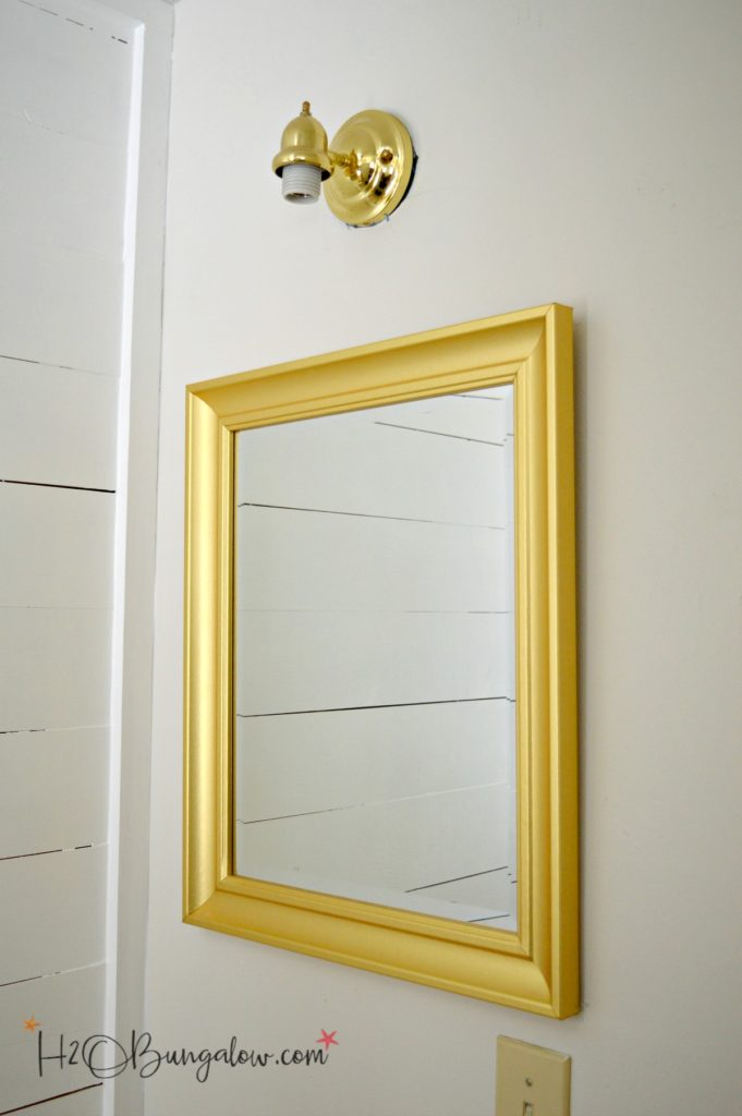 bathroom mirror and light fixture in brass