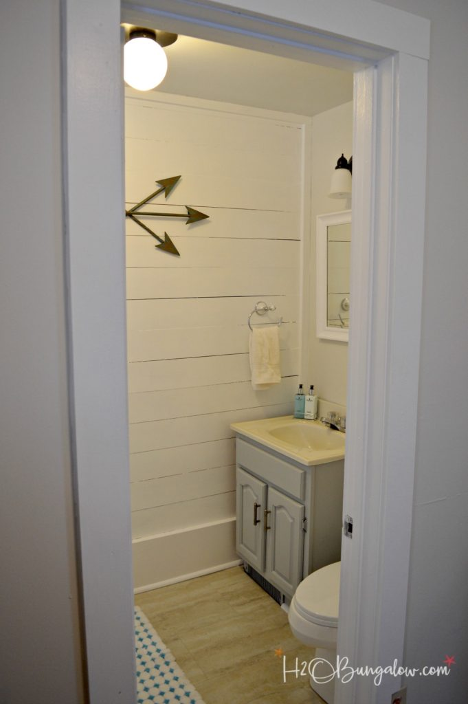 completed bathroom with shiplap walls white mirror and bronze light fixture