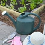 watering can, hat and gloves sitting on ground next to the DIY raised garden bed