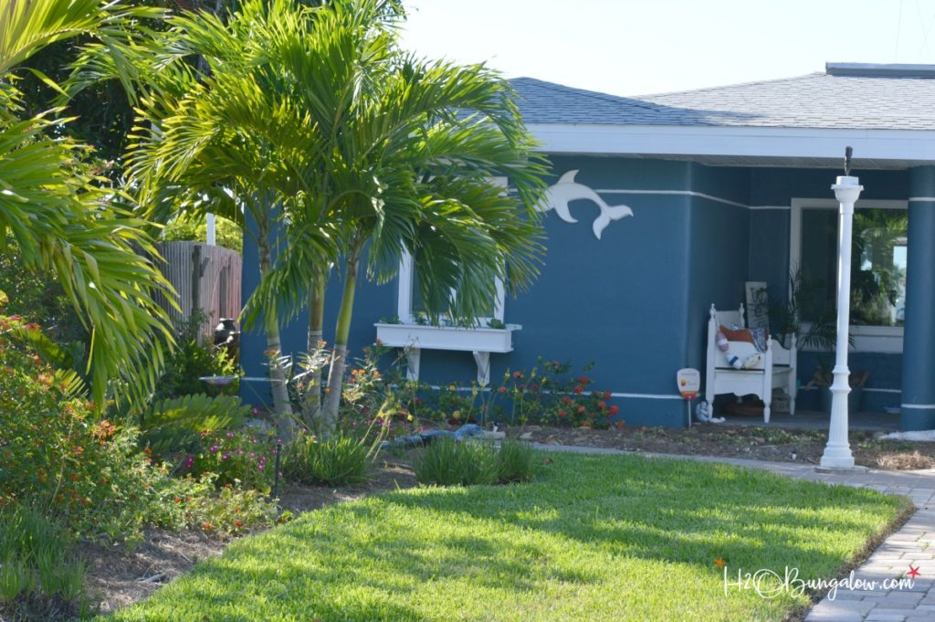 front of house with palm trees and butterfly garden
