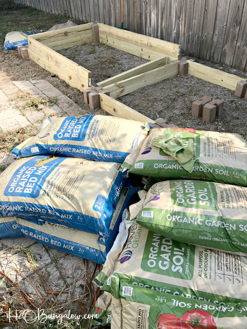bags of organic soil laying next to completed raised garden bed frames