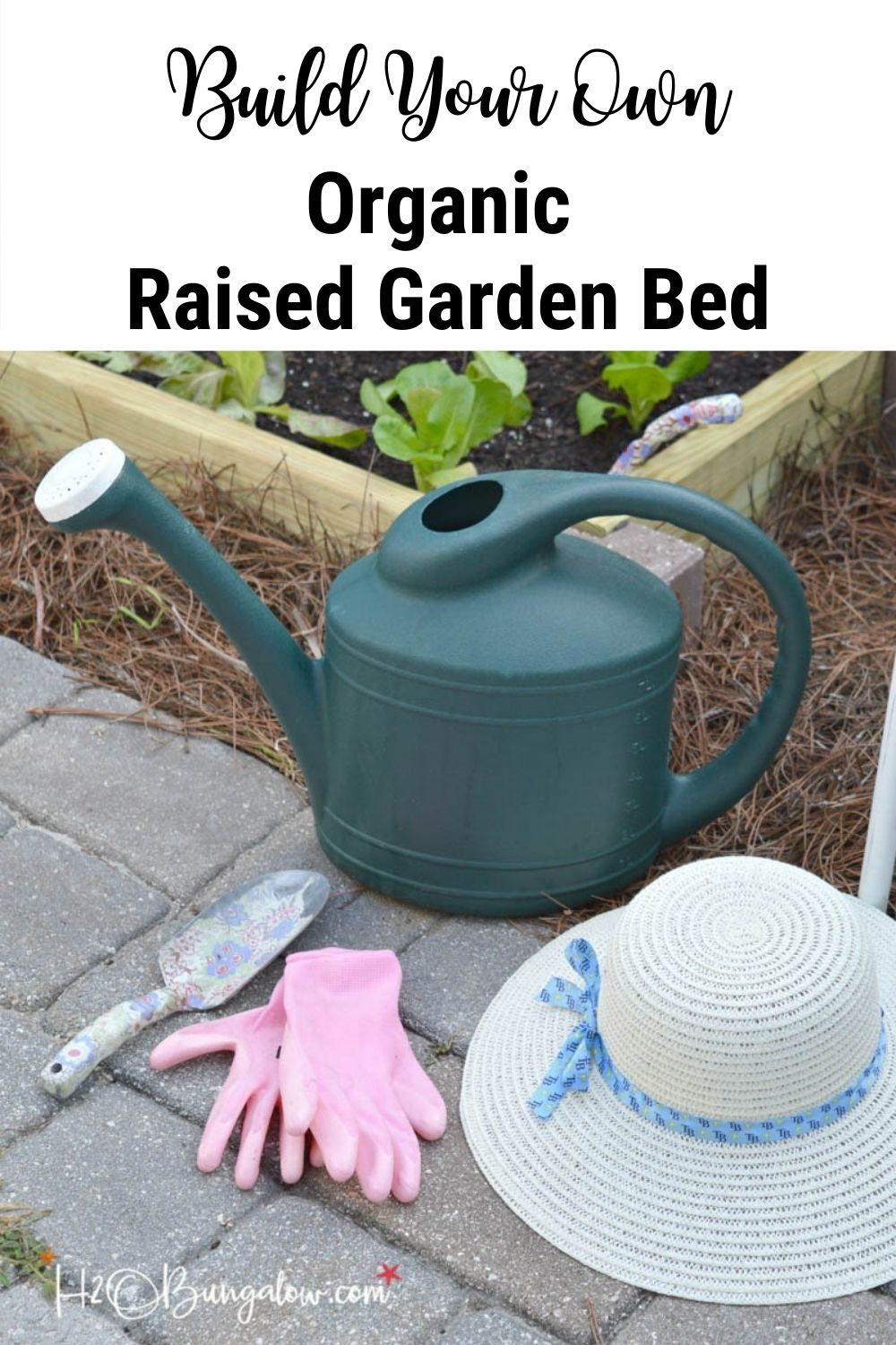 watering can, hat, pink gardening gloves and spade in front of raised garden bed