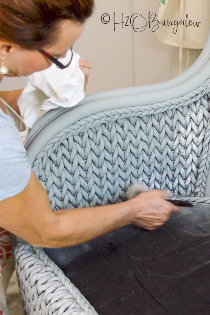 apply paint by hand for detail to wicker chair