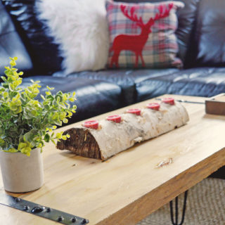 Birch log with five red tea lights sitting on wood coffee table