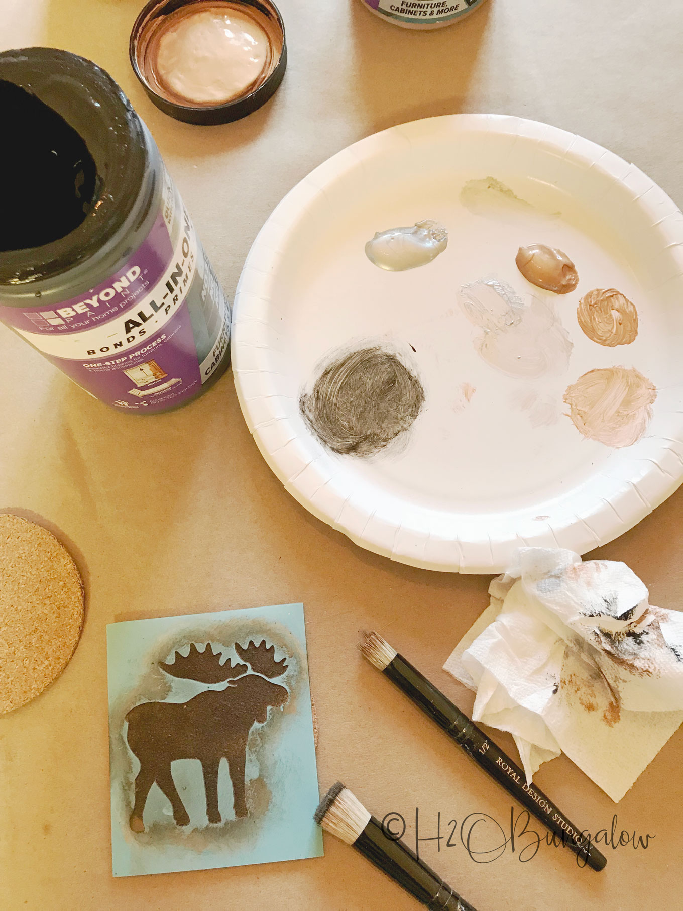 Paint colors on paper plate with moose stencil and small paintbush