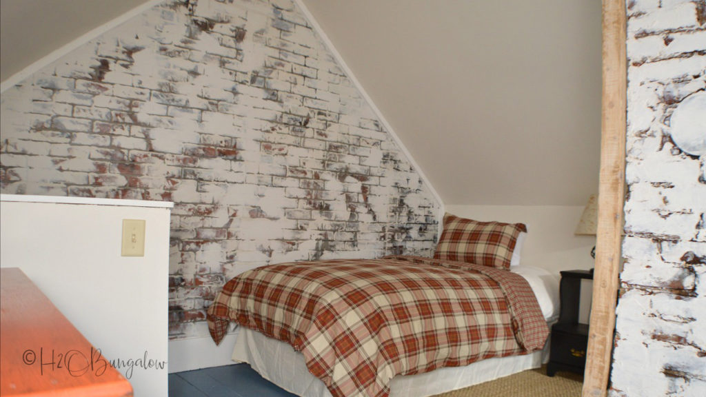 Brick wall with white german schemer with bed and red checked bedspread in front of it.