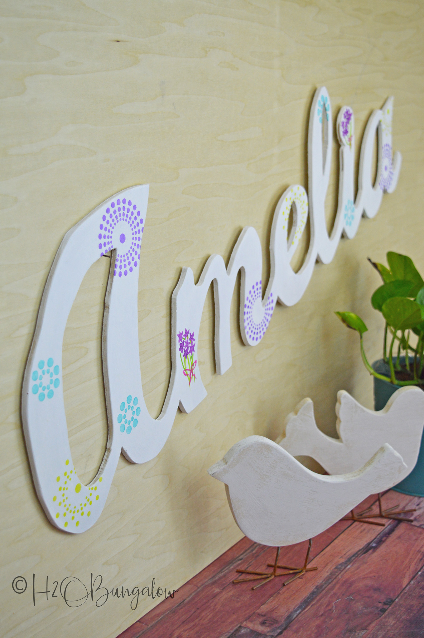 "Tutorial to make a DIY large wood name cut out. Easy project to make using a 1/4"" piece of scrap plywood, a jigsaw and a palm sander.  I've cut large script letters out of wood before and have a good tutorial which I link to below.  This post shares more tips for making clean cuts when cutting out words with a jigsaw."
