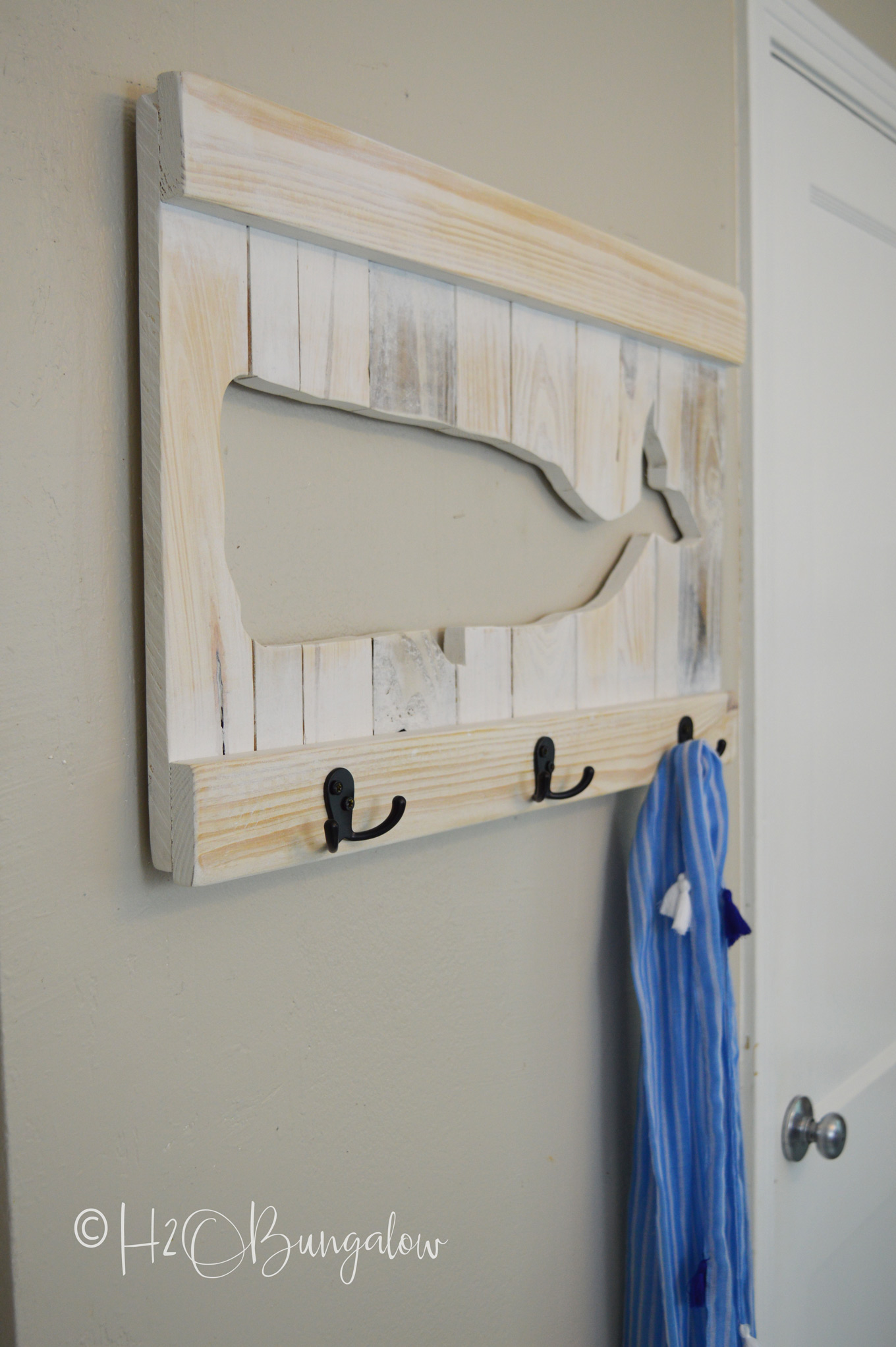 You can easily make a DIY whale coat rack or towel rack for beach towels like mine out of pallets or scrap wood. Follow my instructions for a wood cut-out whale and use your own design to make a sturdy custom coat or towel rack that fits your decor style!