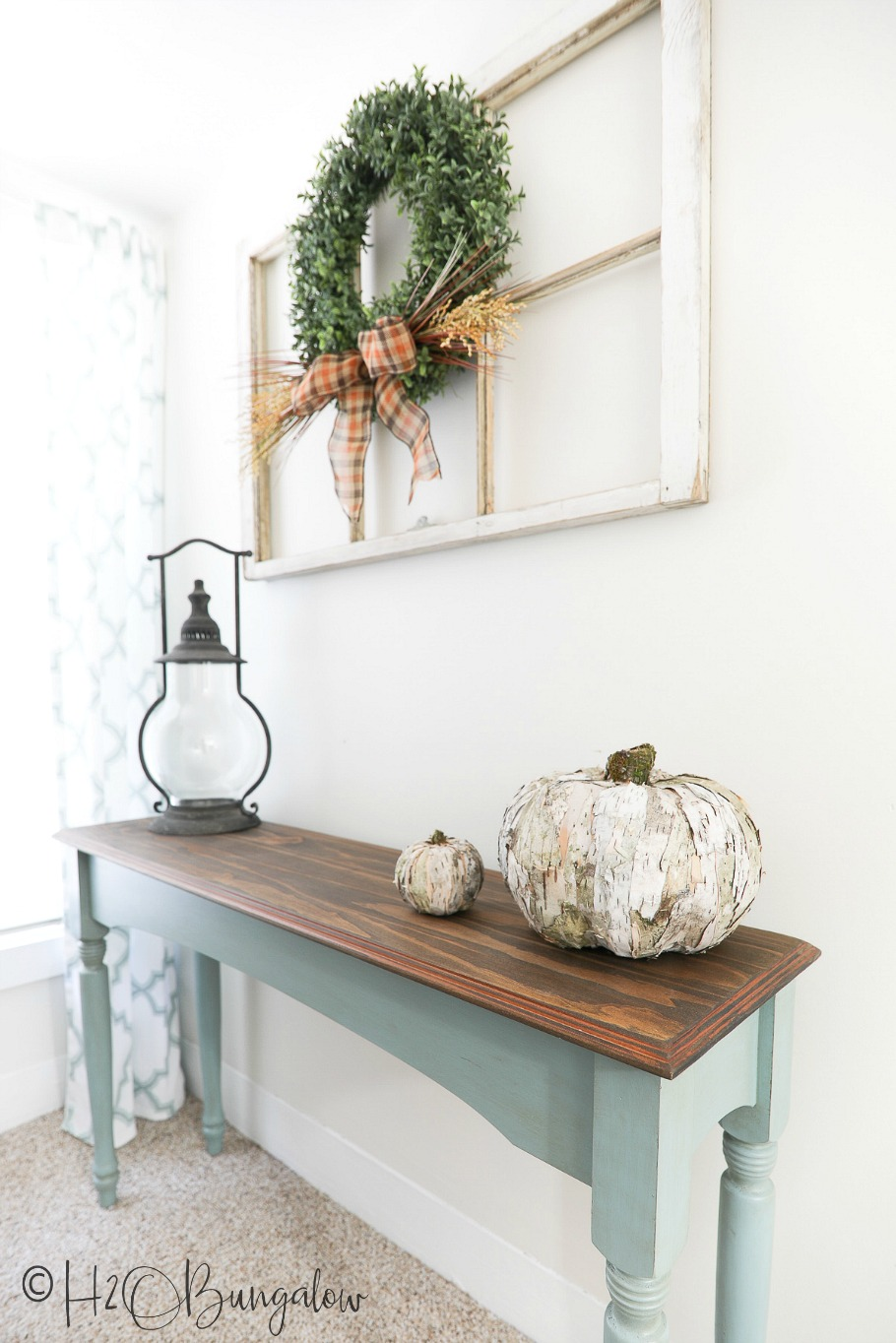 Birch bark pumpkin sitting on console table with lantern and box wreath hanging above on old window.