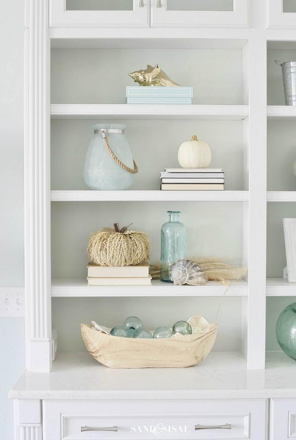 bookcase decorated with coastal fall decor ideas