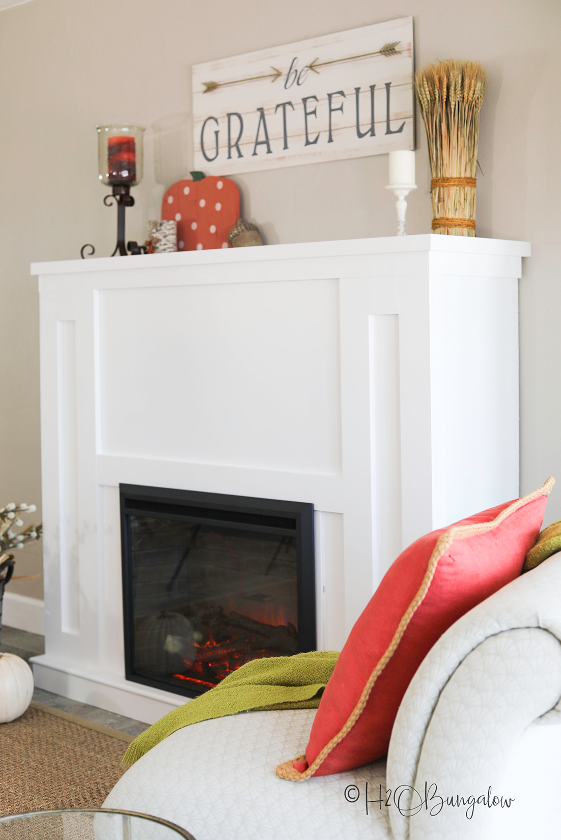 white diy fireplace with electric insert shown with be grateful sign and pumpkin