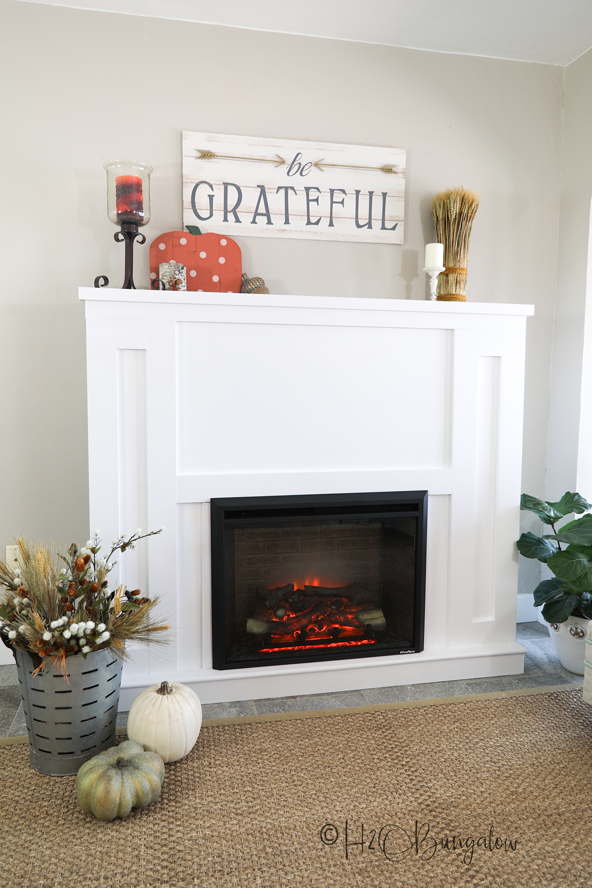 completed DIY fireplace with an electric insert shown with be grateful sign