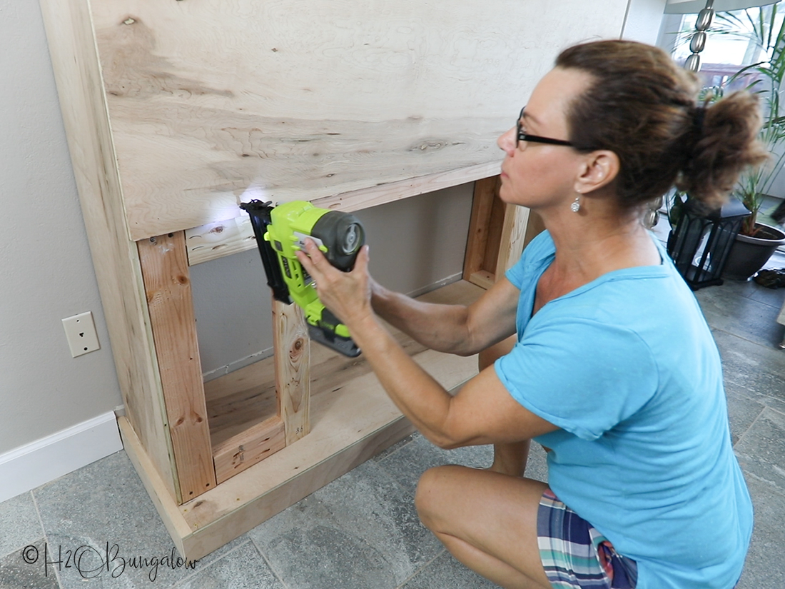 how to add plywood over DIY fireplace frame shown being installed