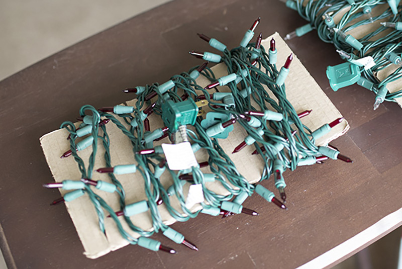 Christmas string lights wrapped on cardboard for storing
