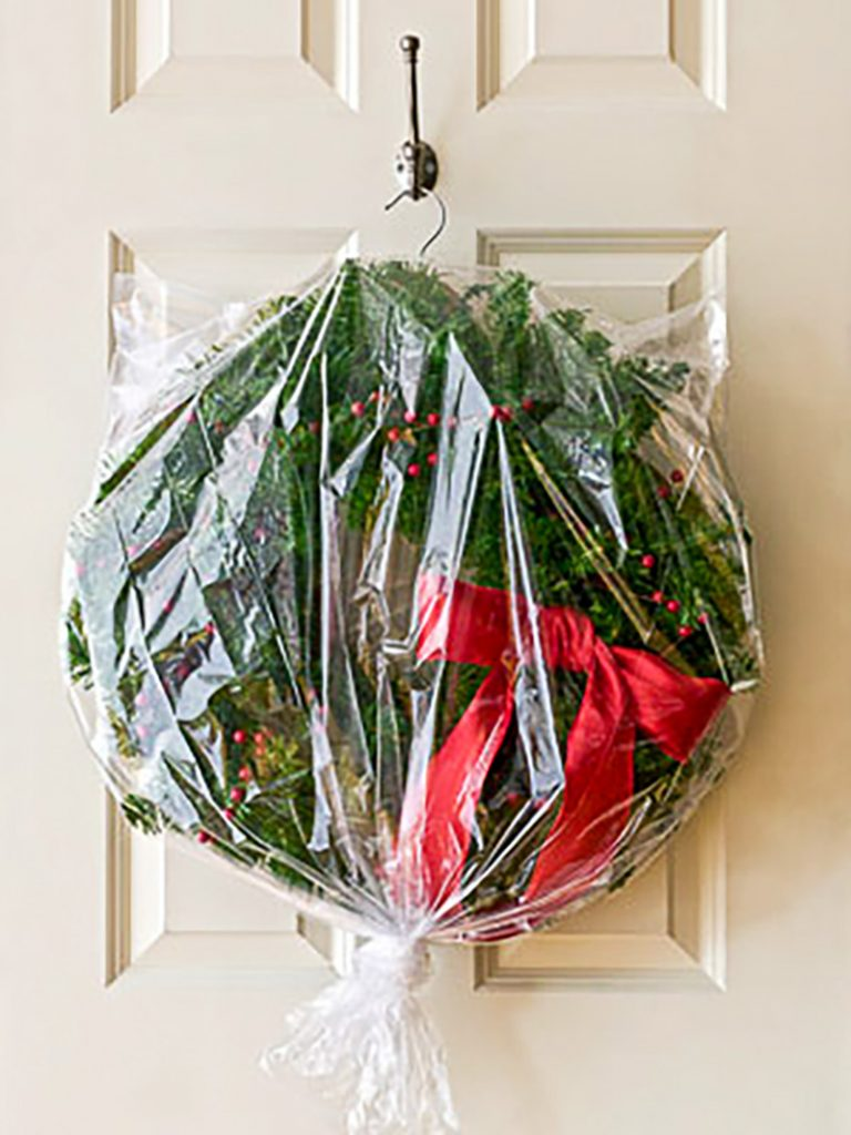 Christmas wreath with red bow in plastic bag hanging on a hook for storage